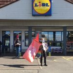 "IWW members standing outside a supermarket, holding flags and flyers. The sign above the supermarket says ""Lidl""."