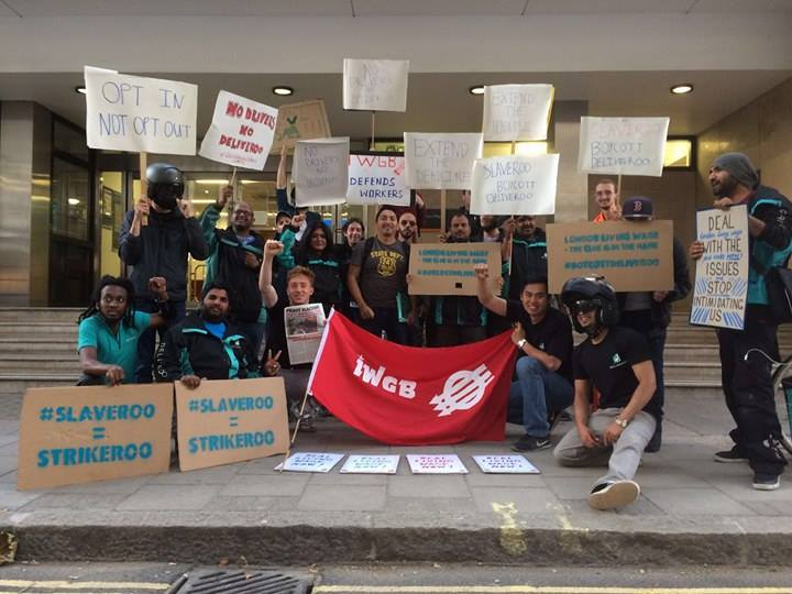 Striking Deliveroo workers holding banners with IWWGB in centre